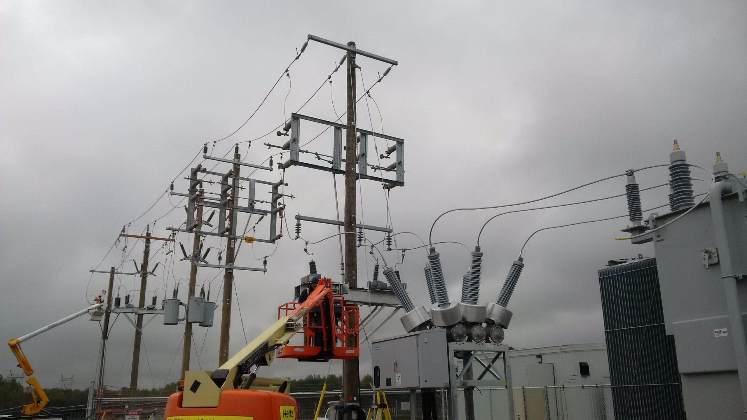 Two linesmen work from articulating man-lift in rear and telescopic boom man-lift front connecting transmission lines to HONI grid