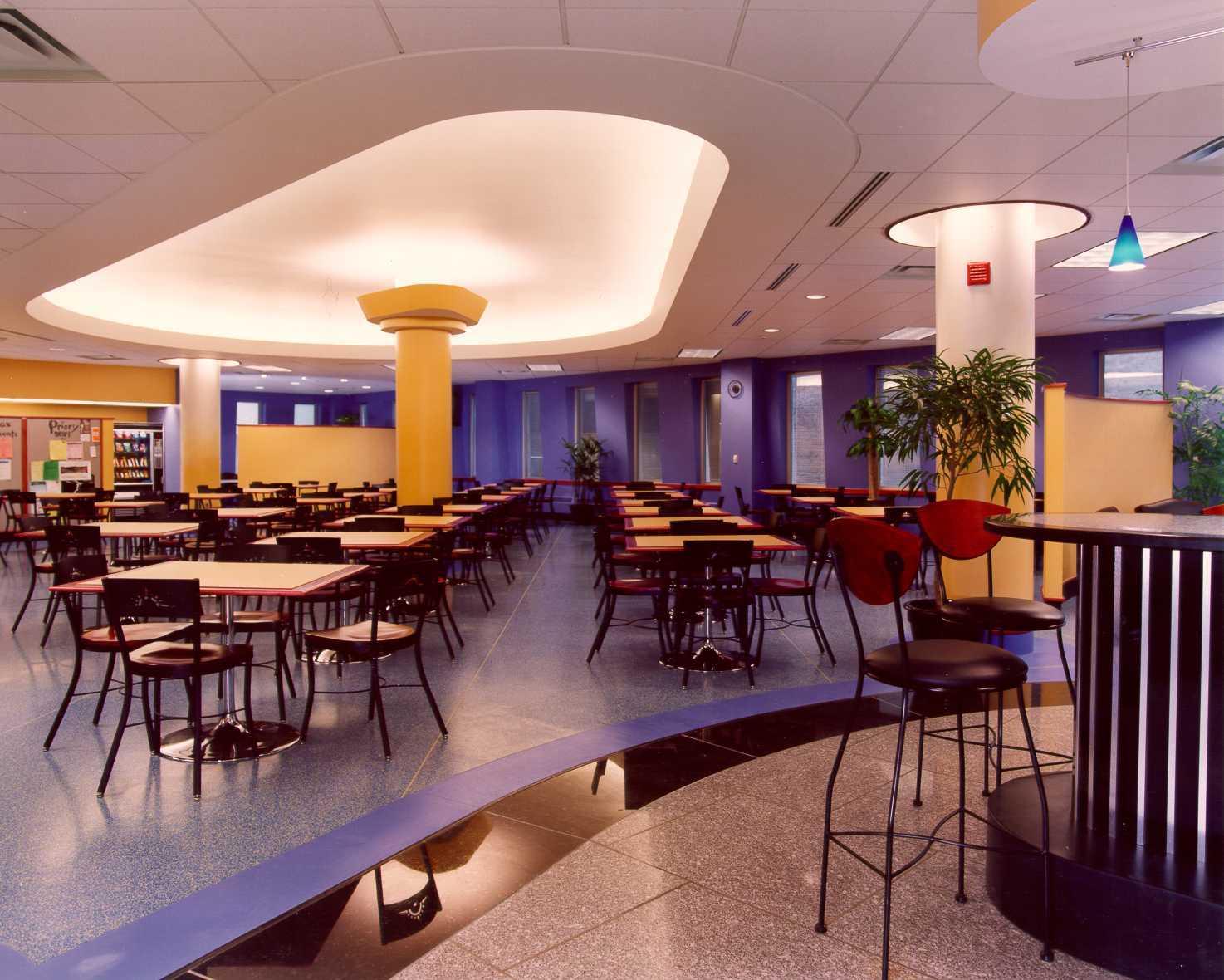 A colorful cafeteria with a plaster compound radius bulkhead, indirect lighting, granite accent flooring