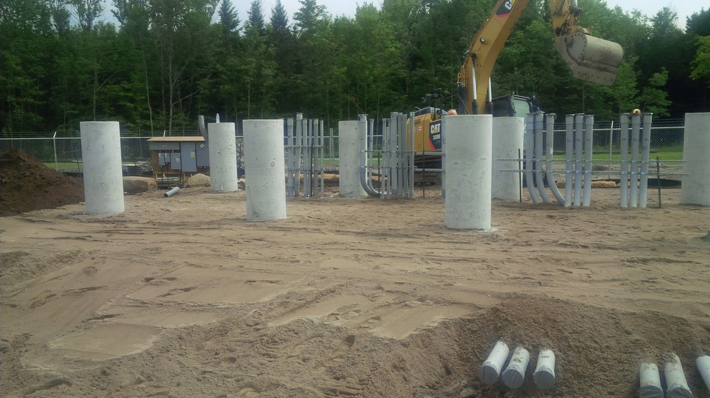 Excavator grading granular material around foundation piers and electrical conduit for a utility-scale solar substation