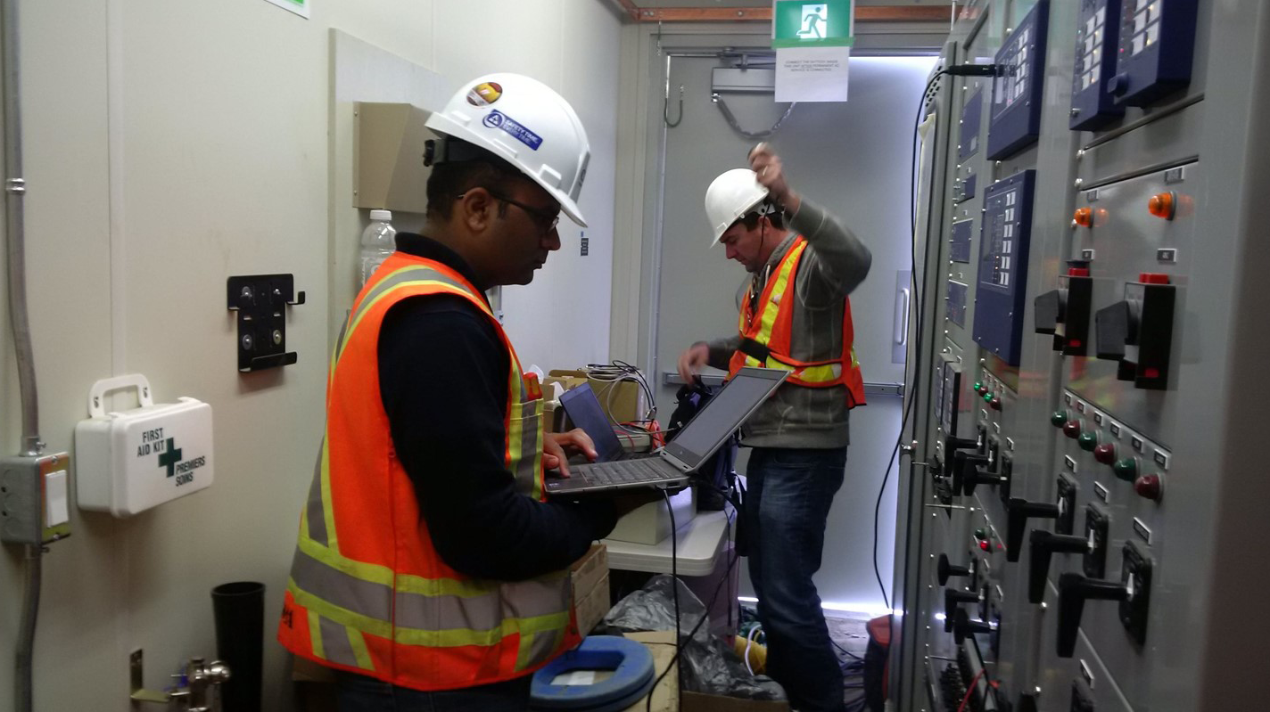 Two workers wearing PPE busy testing equipment in utility-scale solar substation
