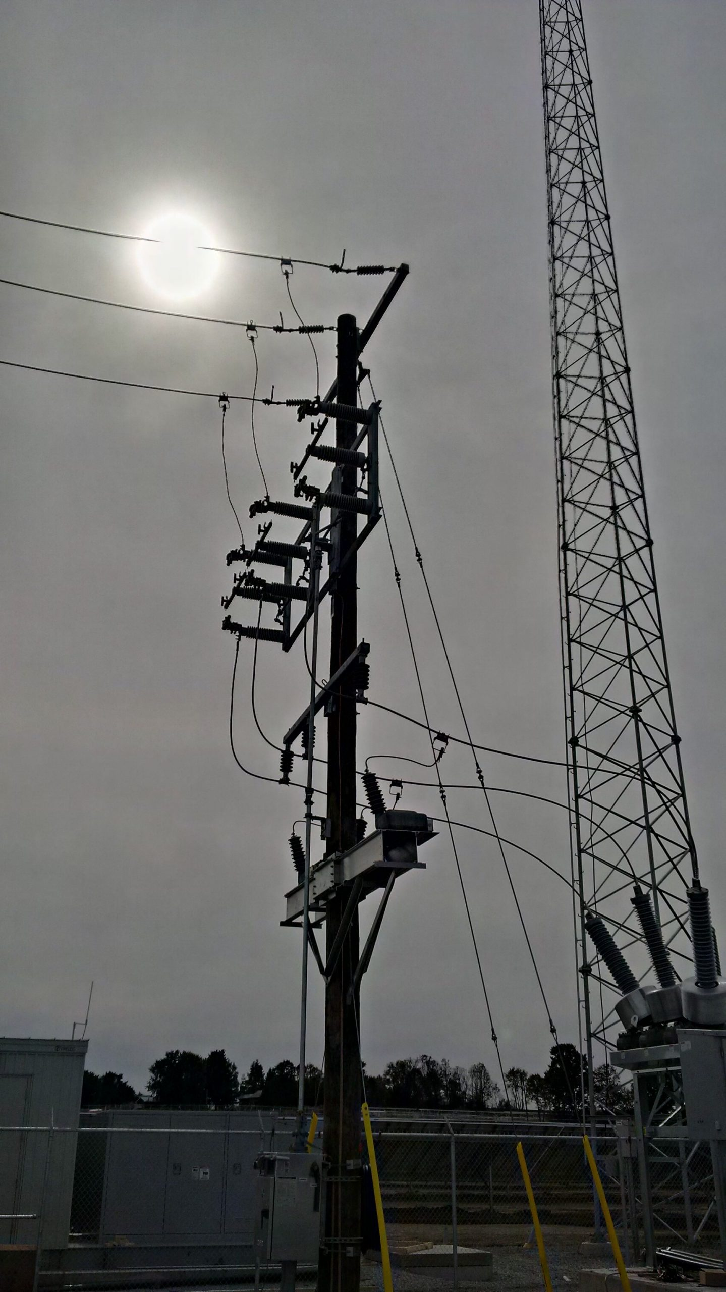 Communication Tower, main circuit breaker, line switches on hydro pole. grey sky with sun