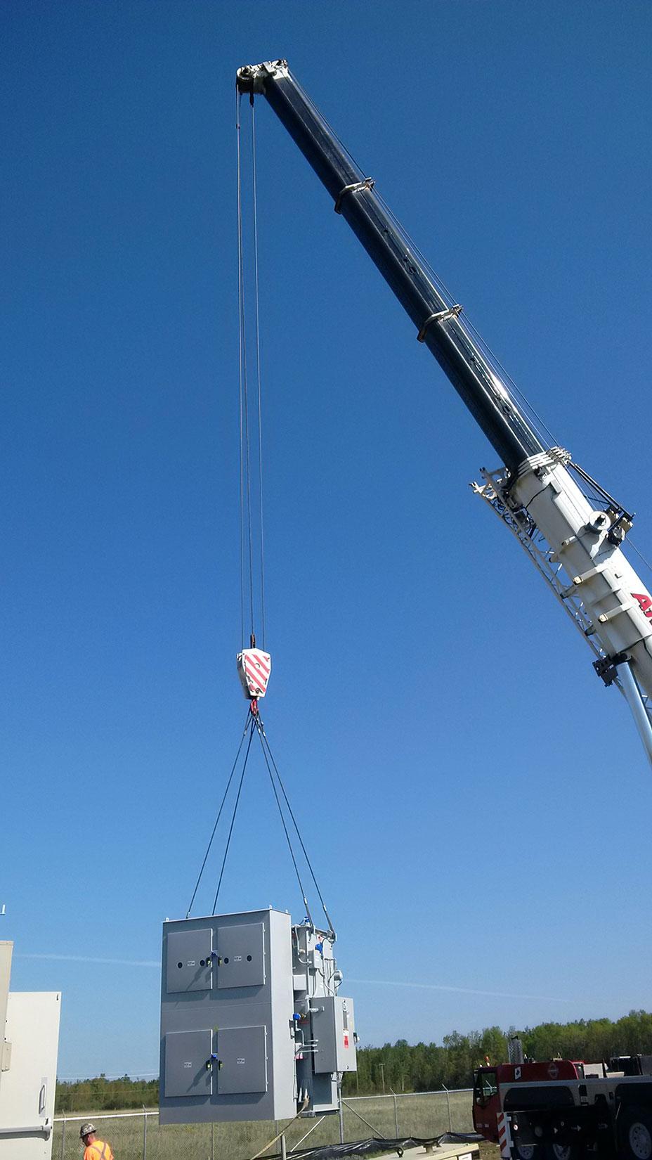 crane lifting distribution transformer for solar farm